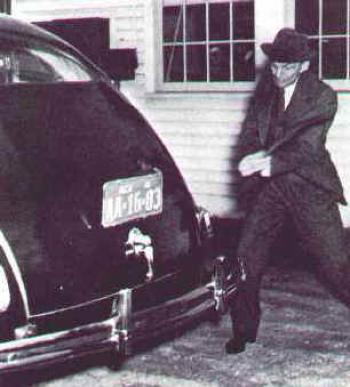 Henry Ford hits the soy plastic car body of his soy car with an axe